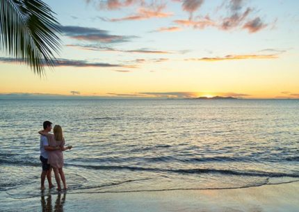 Couple enjoying a beachside sunset on a Fiji weekend getaway