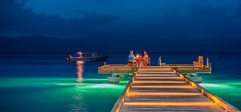 Couple dining on pier at Jean-Michel Cousteau Resort Fiji resort